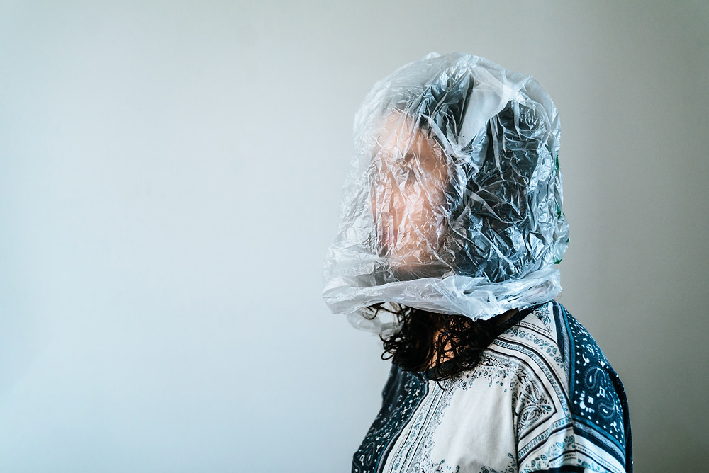 Woman standing on the right side of the frame looks away from camera and has a plastic bag over her head. We are suffocating in plastic.
