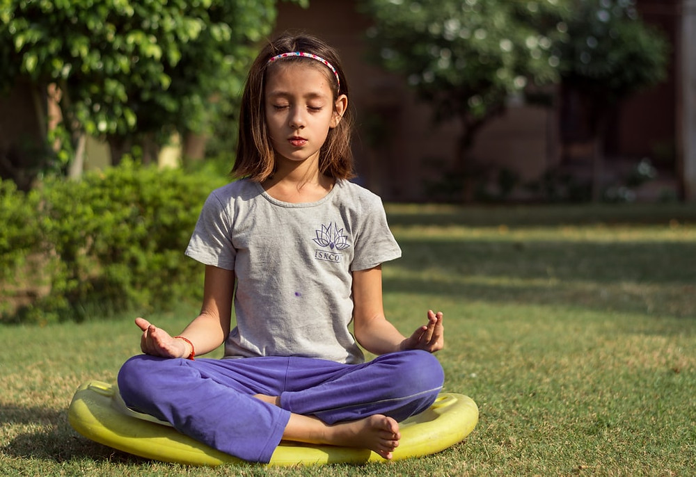 little girl wearing purple pants seated in a meditation cushion in a cross-legged meditation position with her fingers in a mudra.