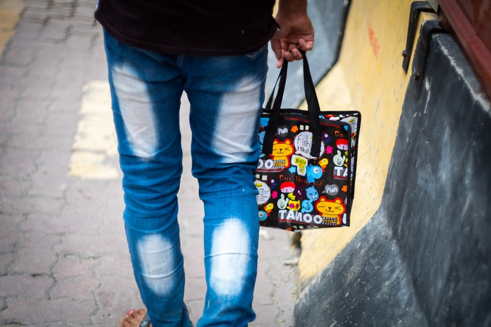 back shot of person wearing faded jeans holding a reusable polyethylene bag