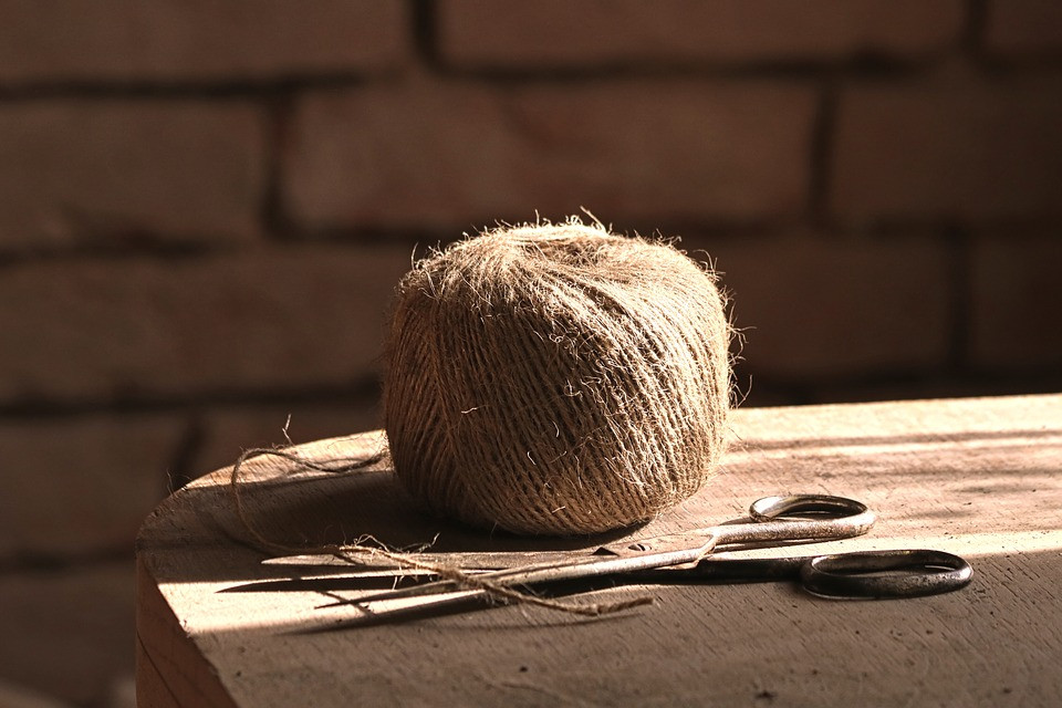 jute yarn spindle resting on a wooden table next to a pair of scissors