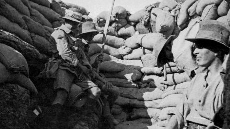 black and white photograph of world war one soldiers sitting in trenches made of jute sandbags