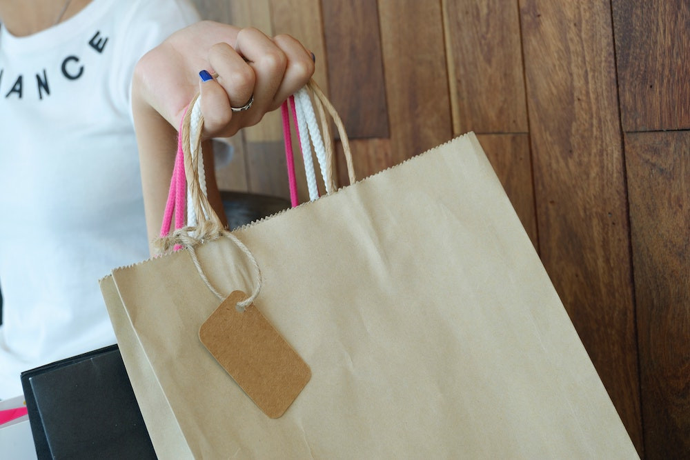 A girl wearing a white shirt is holding gift bags, top-most bag is a brown paper bag