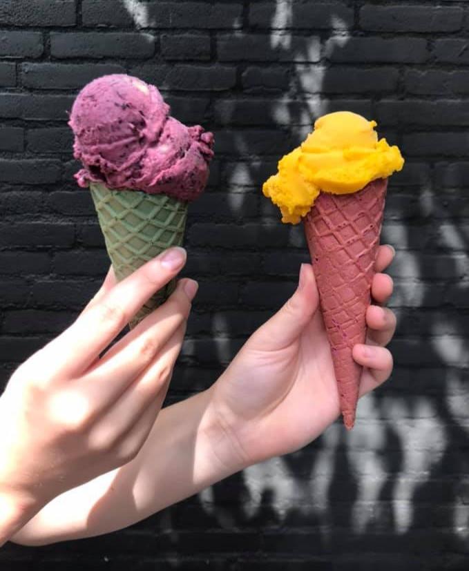 twee ijs hoorns met mango ijs en bosbessen ijs vastgehouden door twee handen