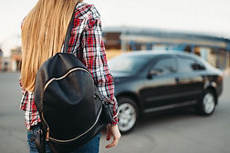 young-woman-driver-with-bag-against-a-ca