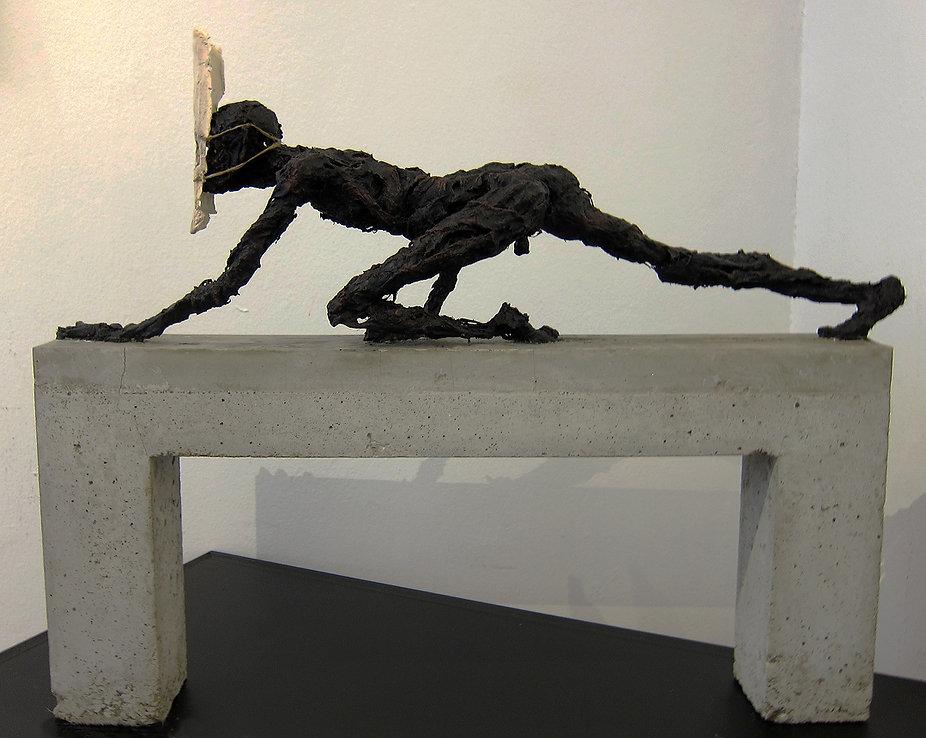 Shadow n°2 - Crawling man on a concrete bridge.