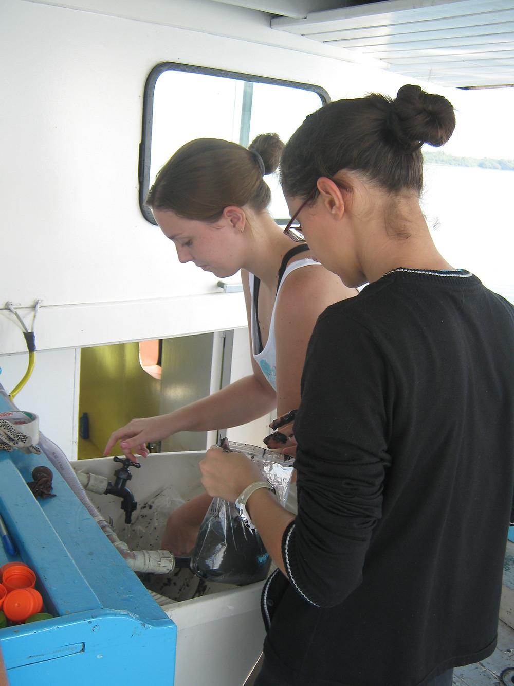 A foto mostra a autora Iara Scricco e sua amiga Carla Elliff lavando materiais de coleta científica em uma pia de um barco. Ambas estão com o cabelo preso em coque. Carla está com uma regata branca e Iara com um casaco preto, segurando um saco ziplock com sedimento