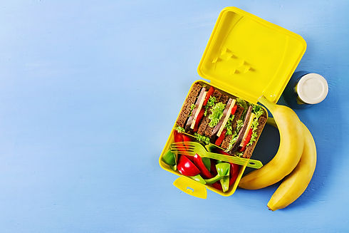 healthy-school-lunch-box-with-beef-sandwich-fresh-vegetables-bottle-water-fruits-blue-back