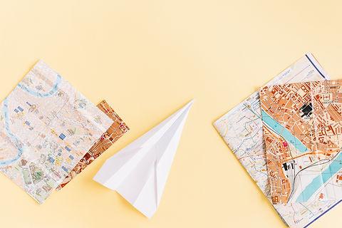 variety-maps-with-white-paper-airplane-beige-background.jpg