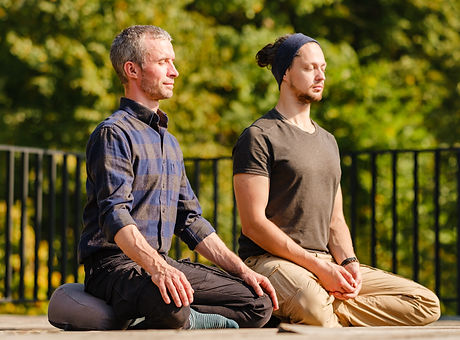 Two young men meditate outdoors in a par