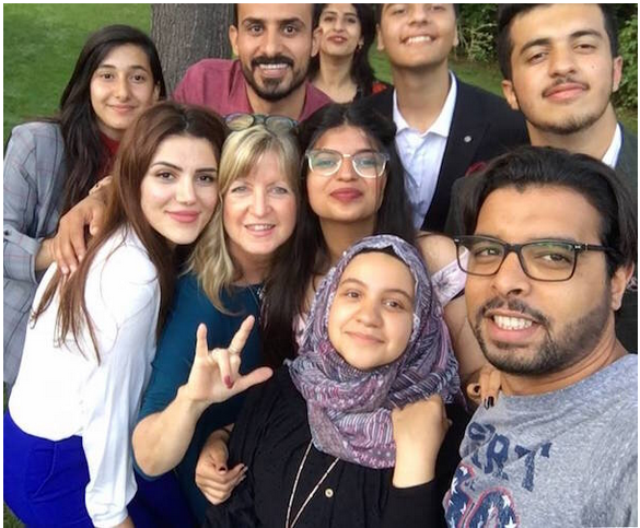 A group of smiling people from a variety of countries smiling.