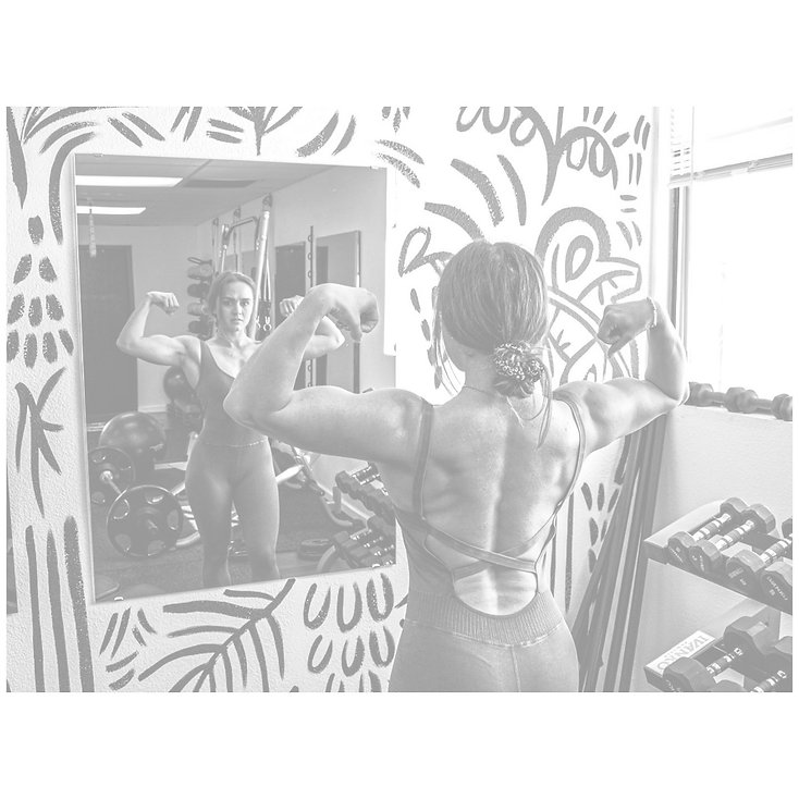girl flexing her arms in front of a mirror in a gym