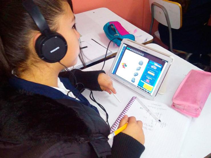 Alumna aprendiendo con UMÁXIMO. Recursos presentes: audífonos, tablet, cuaderno y lápices.