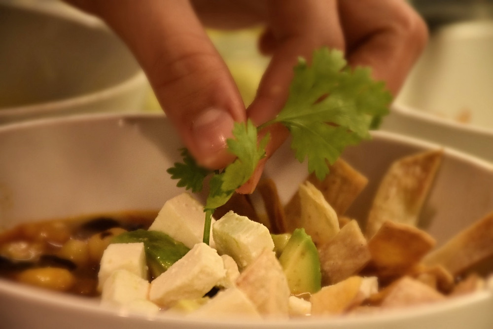 Serving the soup: At the bottom of the bowls put some feta cheese, avocado, chioggia and tortilla strips (leave some of this ingredients to serve astoppings).Serve the soup and top it with the remaining ingredients from the bottom. Garnish with cilantro leaves