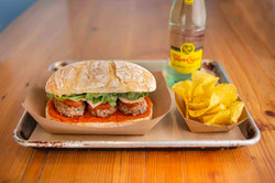Meatball sandwich ptato chips topo chico mineral water.jpeg