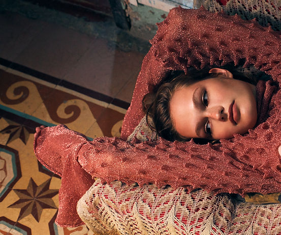 Dasha Malentina in Cuba for Elle Magazine fashion editorial laying on a couch inside a cuban apartment