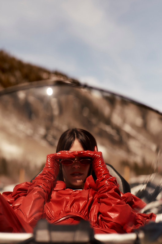 Amand Wellsh wearing in snow up in the mountains of Vail Colorado wearing her red outfit on snowmobile