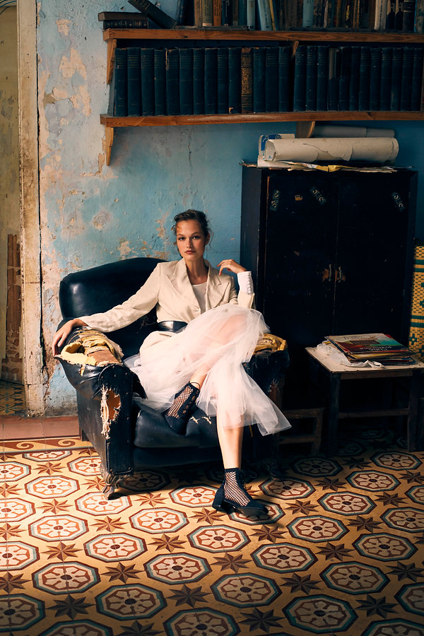 Dasha Malentina in Cuba for Elle Magazine fashion editorial in cuba seating at an old chair ballerina dress