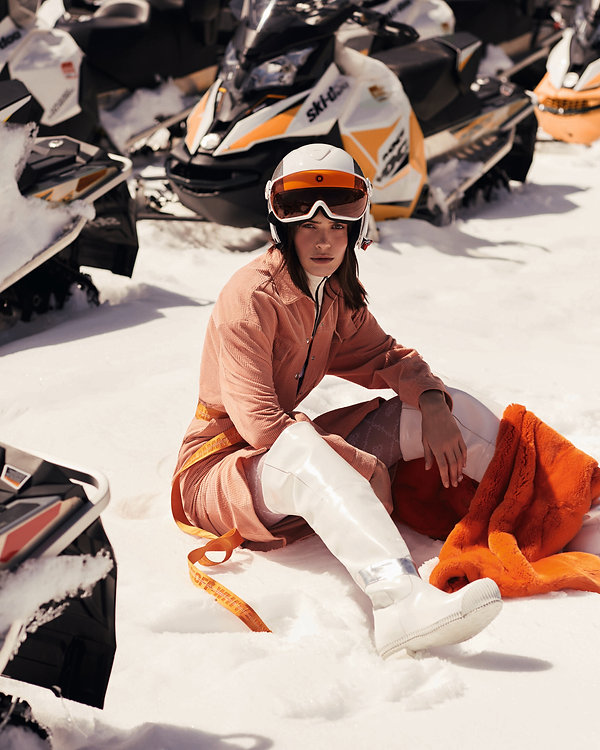 Amand Wellsh wearing Calvin Klein in snow up in the mountains of Vail Colorado, all orange outift snow mobile and helmet