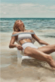 Megan Williams bikini campaign swim at the beach siting on a white chair