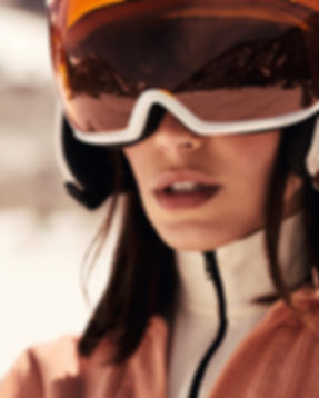 Amand Wellsh wearing Calvin Klein in snow up in the mountains of Vail Colorado, all orange outift snow mobile and helmet portrait