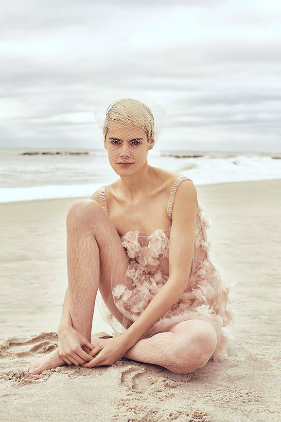 V Magazine March editorial with Taja Feistner or Feistyt at the beach wearing all white clothes seating by the ocean with pink pastel dress casual and with vail