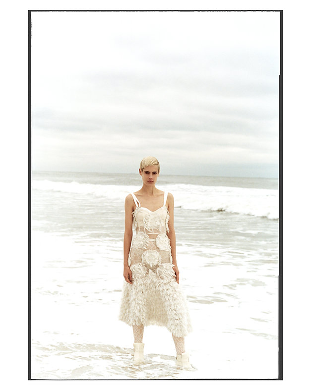 V Magazine March editorial with Taja Feistner or Feistyt at the beach wearing all white clothes inside the water all wet with boots