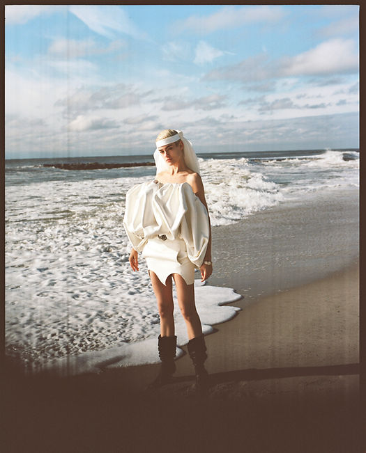 V Magazine March editorial with Taja Feistner or Feistyt at the beach wearing all white clothes wearing saint laurent YSL by the ocean