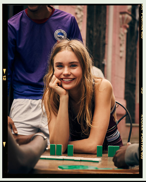 Viva La Revolucion - Will Vendramini - Elle magazine with brooke perry shot in Havana Cuba playing domino with strangers smiling, shot on film