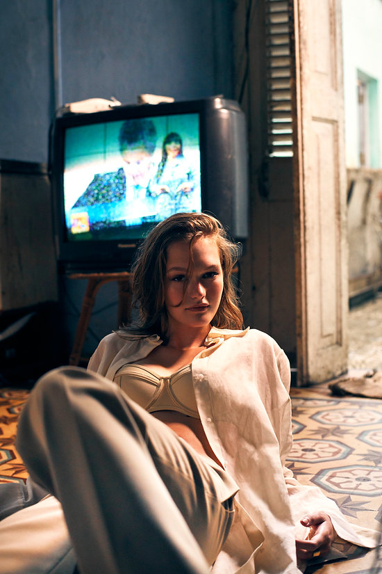 Dasha Malentina in Cuba for Elle Magazine in cuban living room with tv on the back