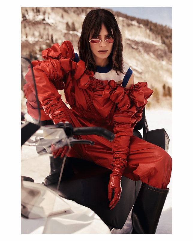 Amand Wellsh wearing  in snow up in the mountains of Vail Colorado wearing red on snowmobile