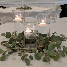 3 cylinders with floating candle and greenery
