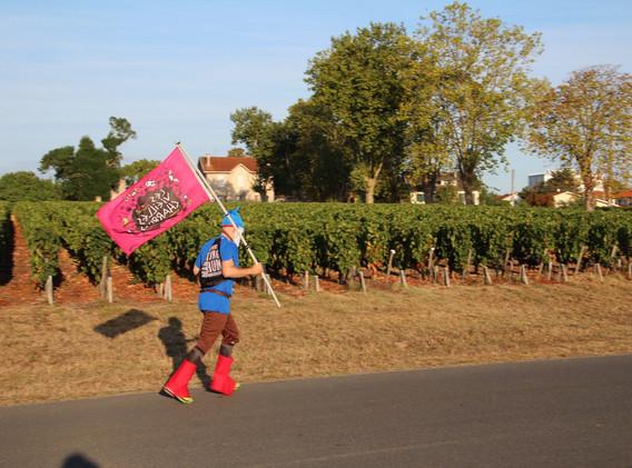 Flag-Bearing Runner at the Marathon du Medoc