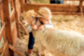 Girl hugging lamb on the farm_edited.jpg