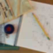 Picture of sketch book, pencil, tape measure, and bank bag