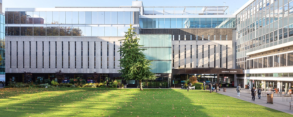 An image of a building on Imperial College London campus. Rectangle shaped building with concrete on the main body and glass windows on the top floors. A grass lawn is in front of the building.