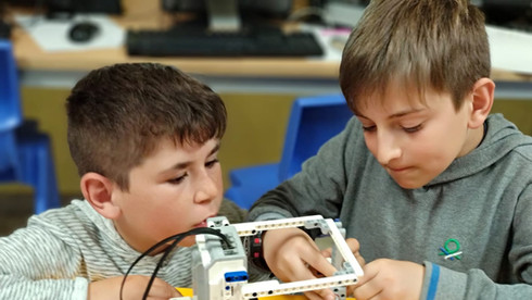 Nens realitzant l'extraescolar de robòtica d'Escola Pia Calella Primària