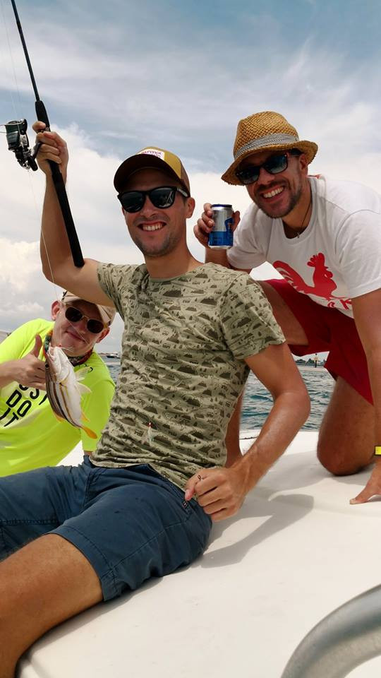 Anglers on fishing yacht with beer and fish