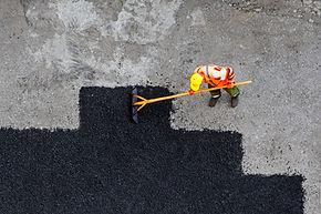 Aerial view of road worker repair asphal