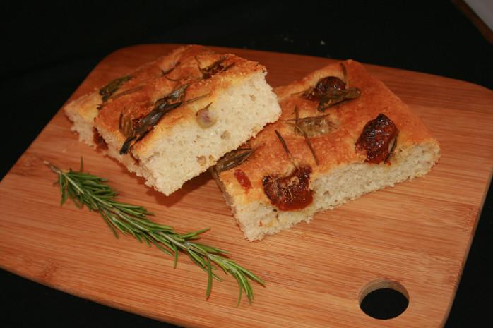 Focaccia au parmesan, tomates séchées, olives vertes, basilic et romarin.