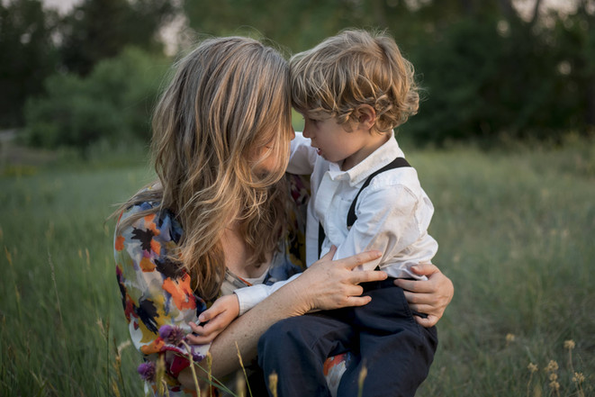 Outdoor family photo shoot, mom and little boy embrace