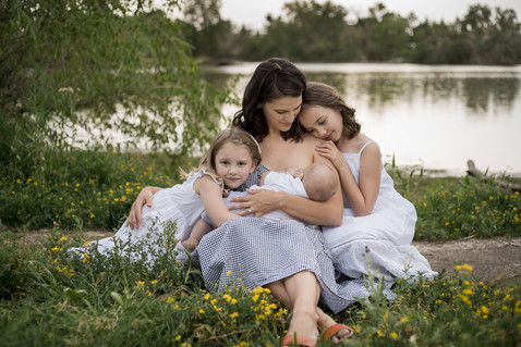 Outdoor family photo shoot, mom nurses while sisters snuggle close