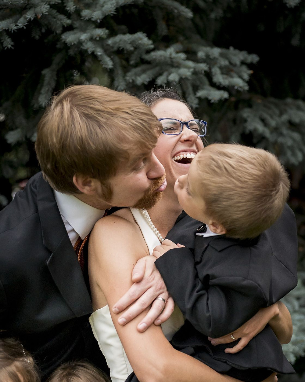 Husband kisses son in mother's arms, laughing, Arvada, Colorado
