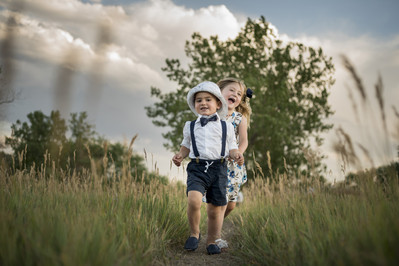 Denver outdoor family photo shoot, brother and sister running through tall grass