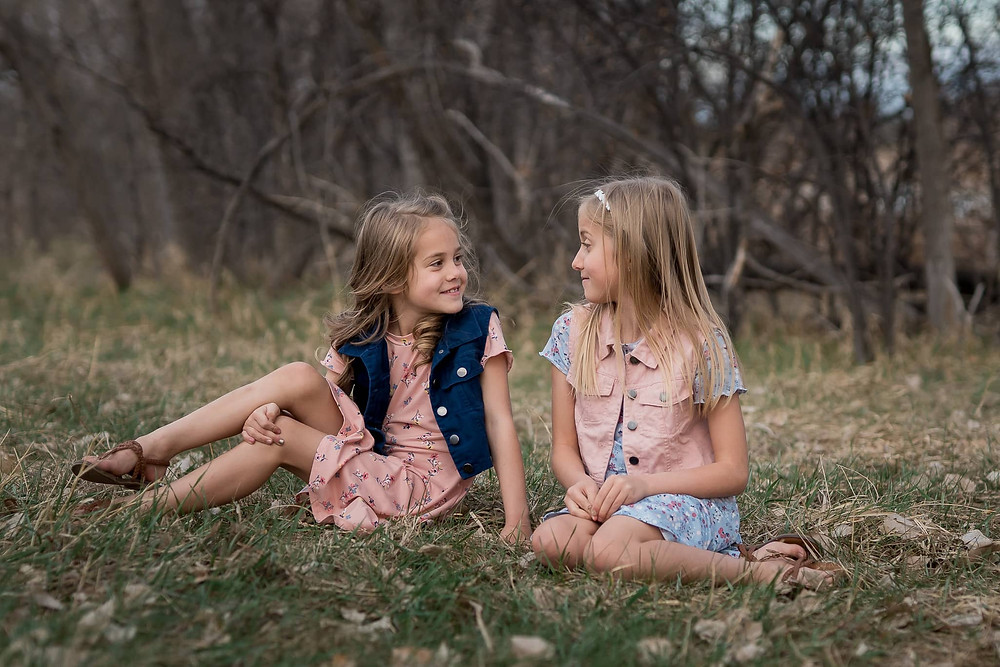 Sisters eye each other in Denver area portrait session