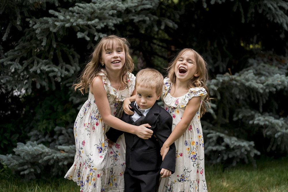 Family photo of sisters hugging younger brother, Arvada, Colorado