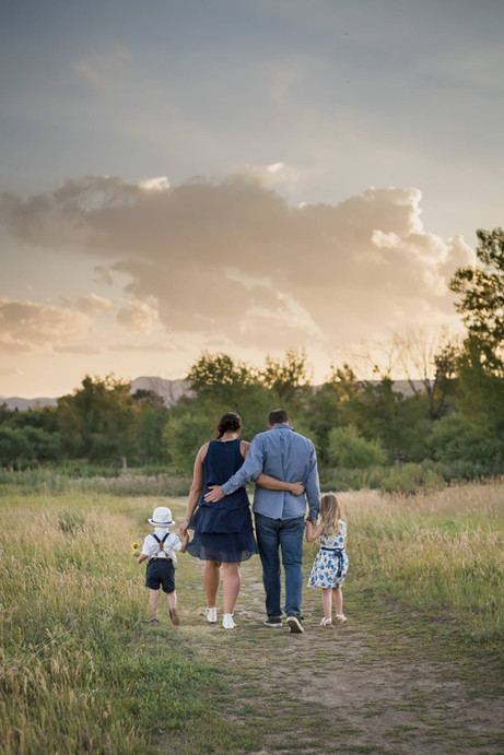 Denver outdoor family photo shoot, family walks away into stunning Colorado sunset