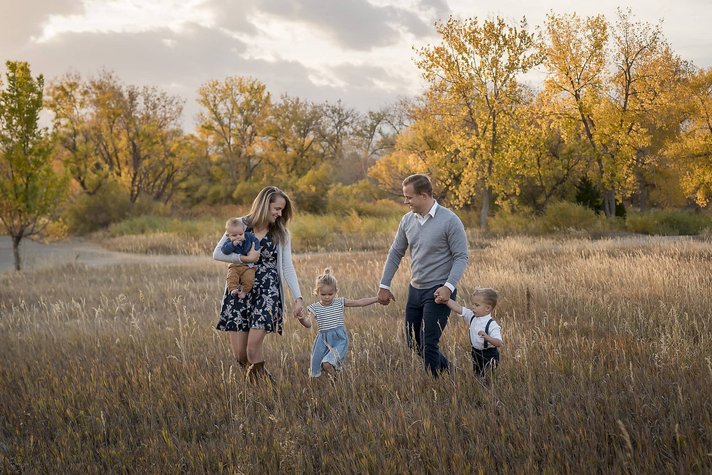 Denver area family photography session, family walking through golden meadow in Colorado sunset