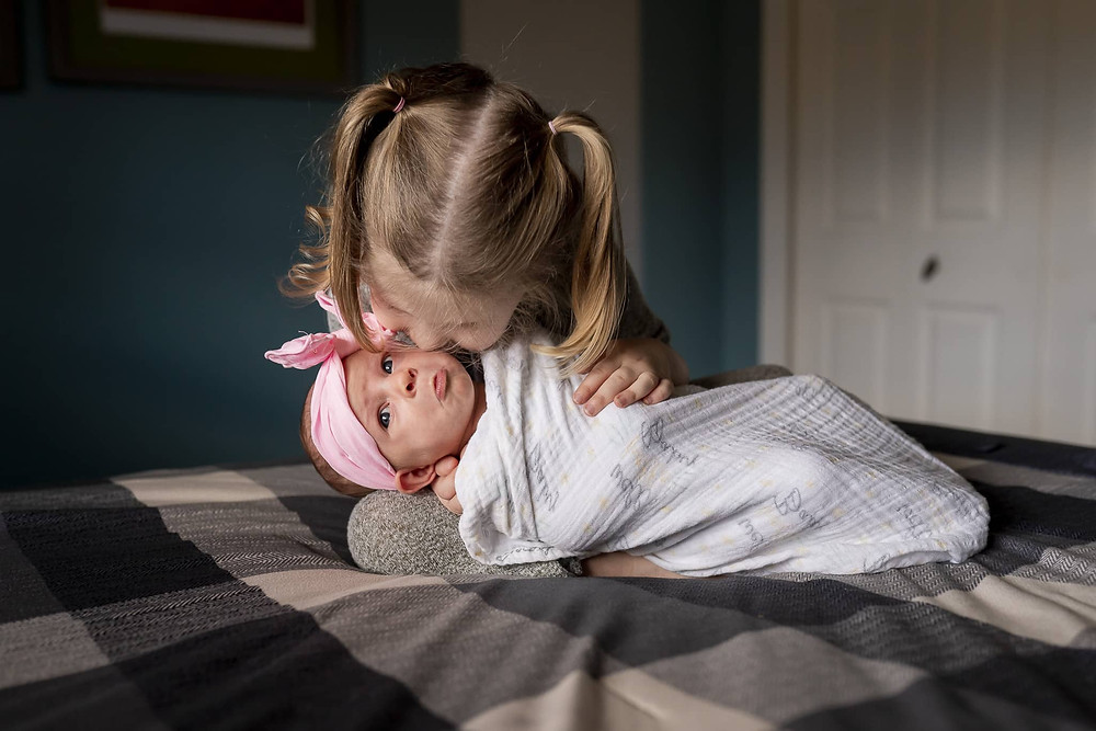 Newborn and sibling in an in-home newborn portrait session