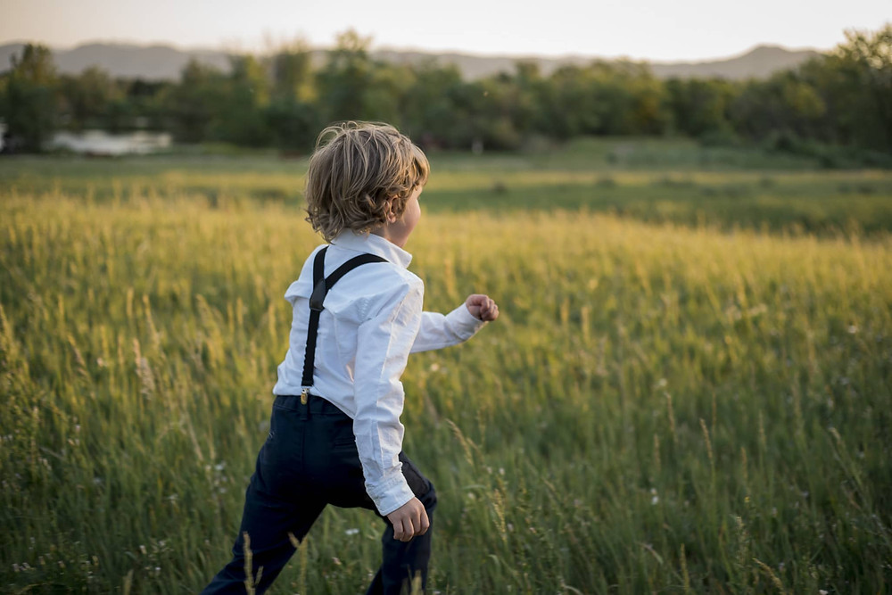 Boy running through meadow at sunset in Lakewood, Colorado