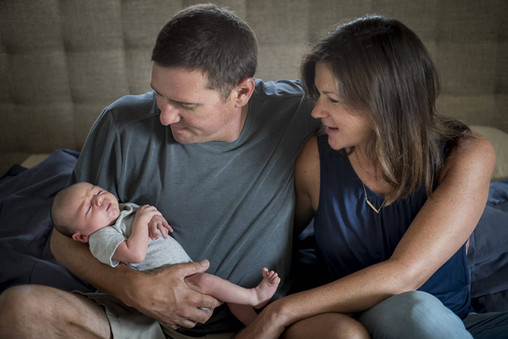 Relaxed in-home newborn photography, baby in dad's arms on bed